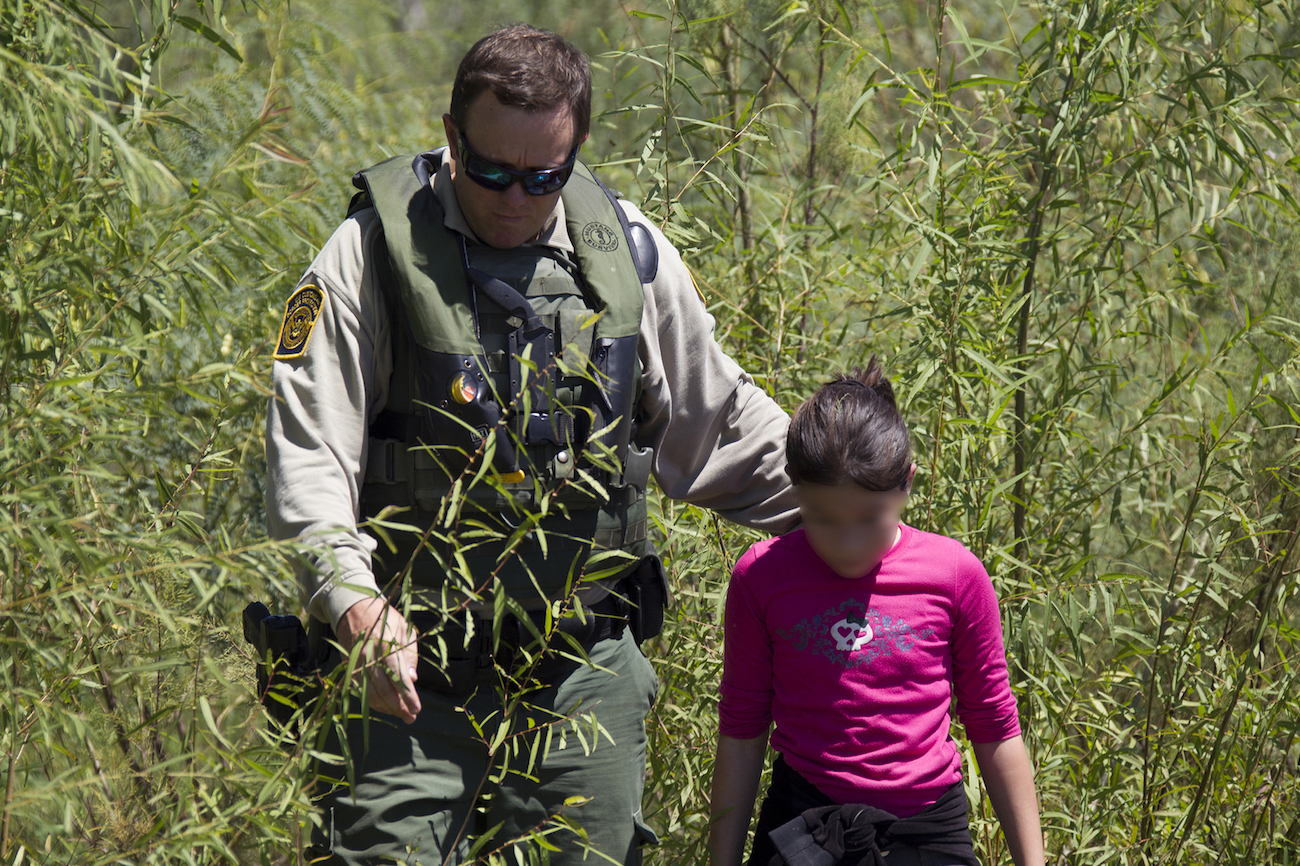 A Border Patrol officer assists a girl stranded on the river bank of Rio Grande in Texas. Photo by Donna Burton/US Customs and Border Patrol.