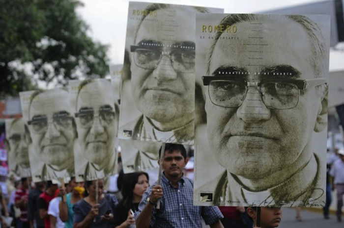 People carry large portraits of Salvadoran Archbishop Oscar Romero during rally in his honor in San Salvador